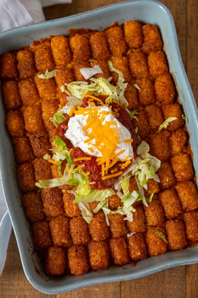 Taco Tater Tot Casserole top down in baking dish with taco meat and cheddar cheese