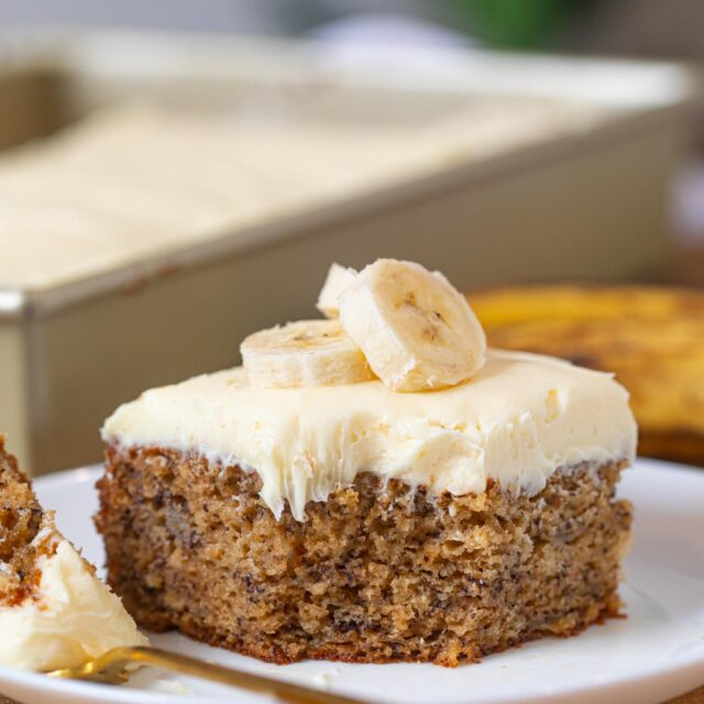 Slice of Banana Cake with frosting and banana slices