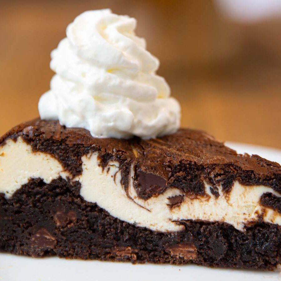 Brownie Cheesecake slice on plate with whipped cream