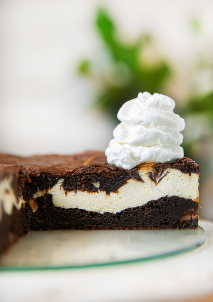 Brownie Cheesecake sliced open with whipped cream