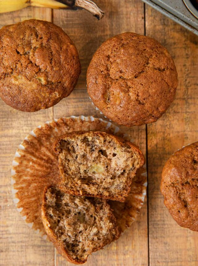 Banana Muffin broken in half in muffin liner on wooden board