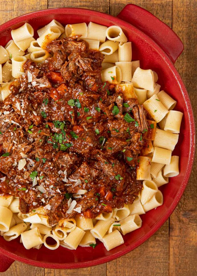 Beef Ragu over short pasta in red bowl