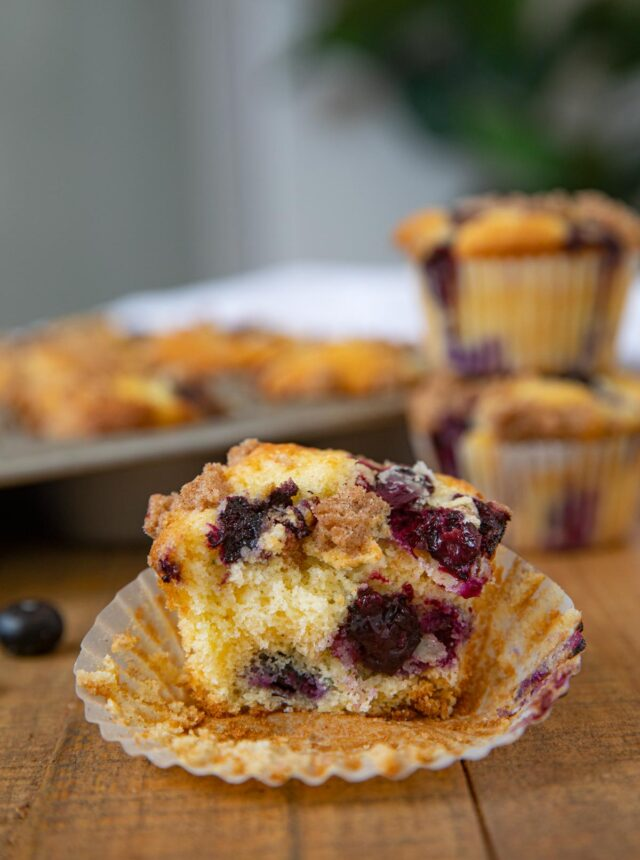 Blueberry Crumb Muffin on board with muffins behind it
