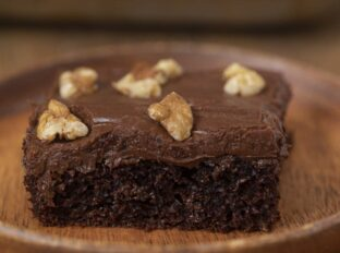 Chocolate Texas Sheet Cake slice on wooden plate