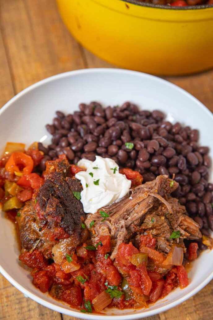 Mexican Pot Roast in bowl with black beans and sour cream