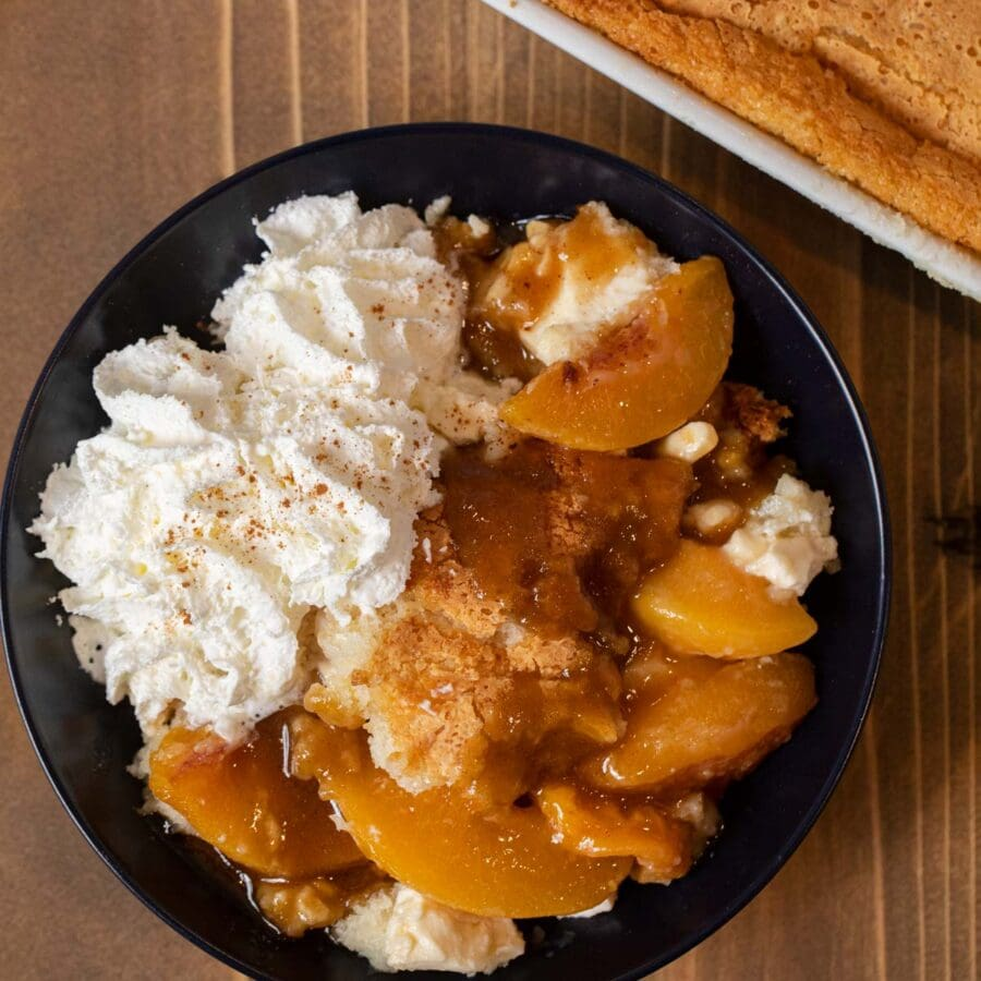 Peaches and Cream Cobbler serving in bowl with whipped cream