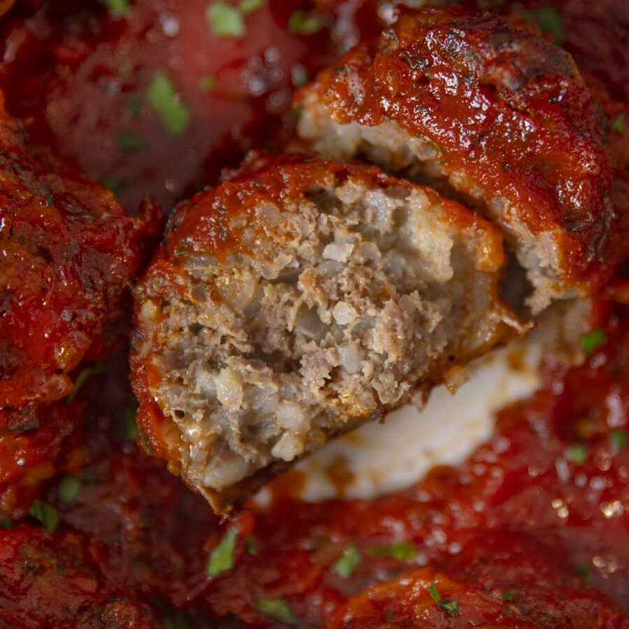 Porcupine meatball covered in marinara sauce with a bite taken out