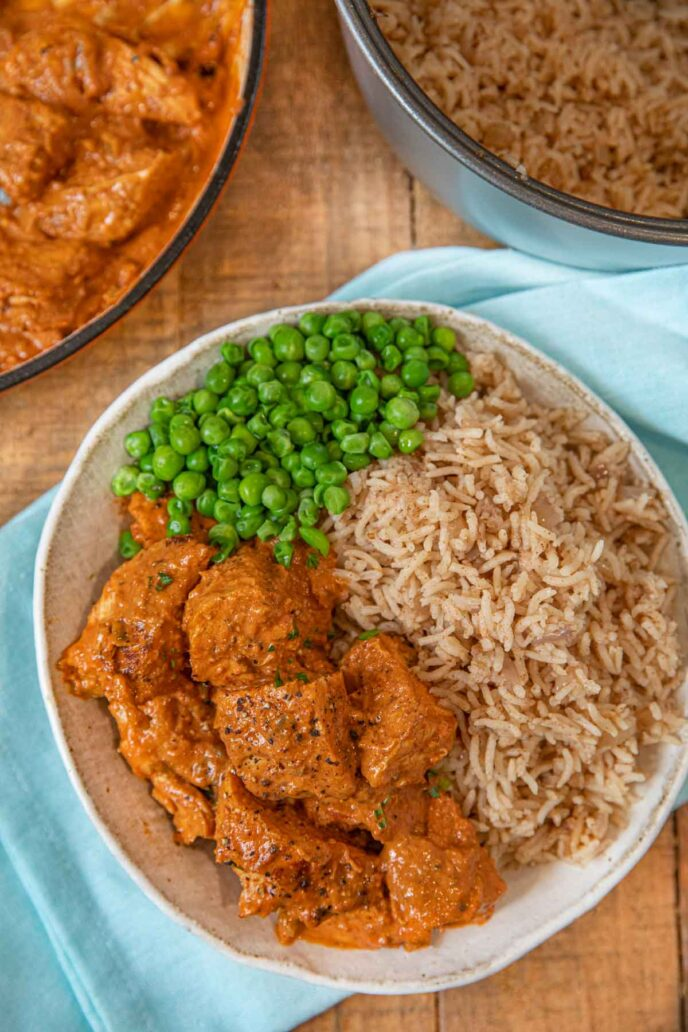 Indian Butter Chicken with peas and rice on plate