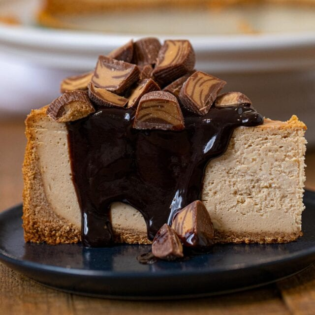 Peanut Butter Cheesecake slice on plate with chocolate sauce and peanut butter cups