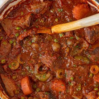 Spanish Beef Stew with large wooden spoon
