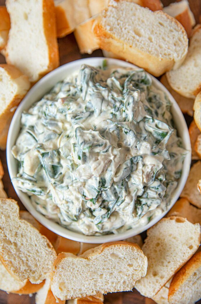 Spimach Dip in bowl with sliced french bread for dipping