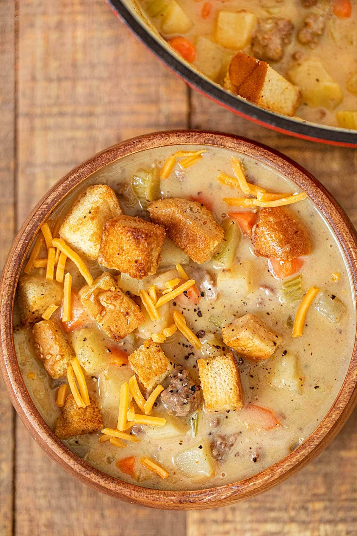 Cheeseburger Soup in wooden bowl with cheese and hamburger bun croutons