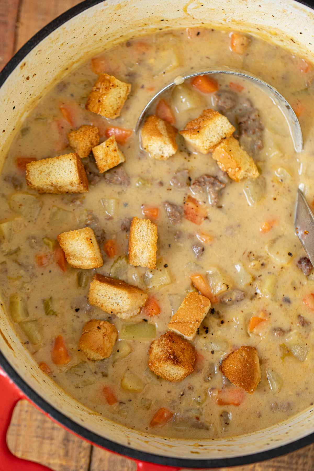 Cheeseburger Soup in pot with hamburger bun croutons and ladle