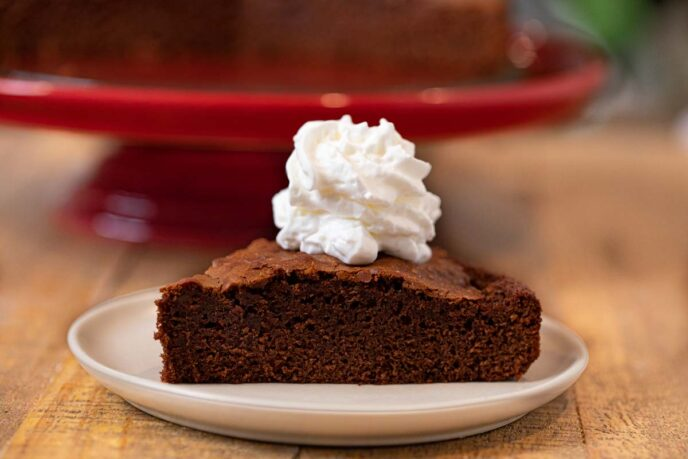 Nutella Cake slice on plate with whipped cream topping