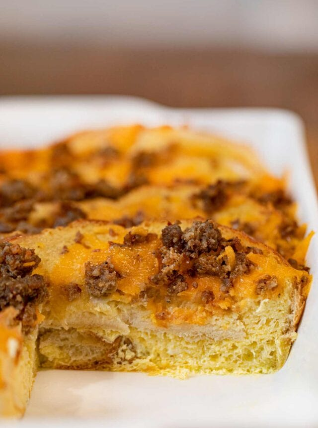 Sausage Cheddar French Toast Casserole in baking dish with slice removed