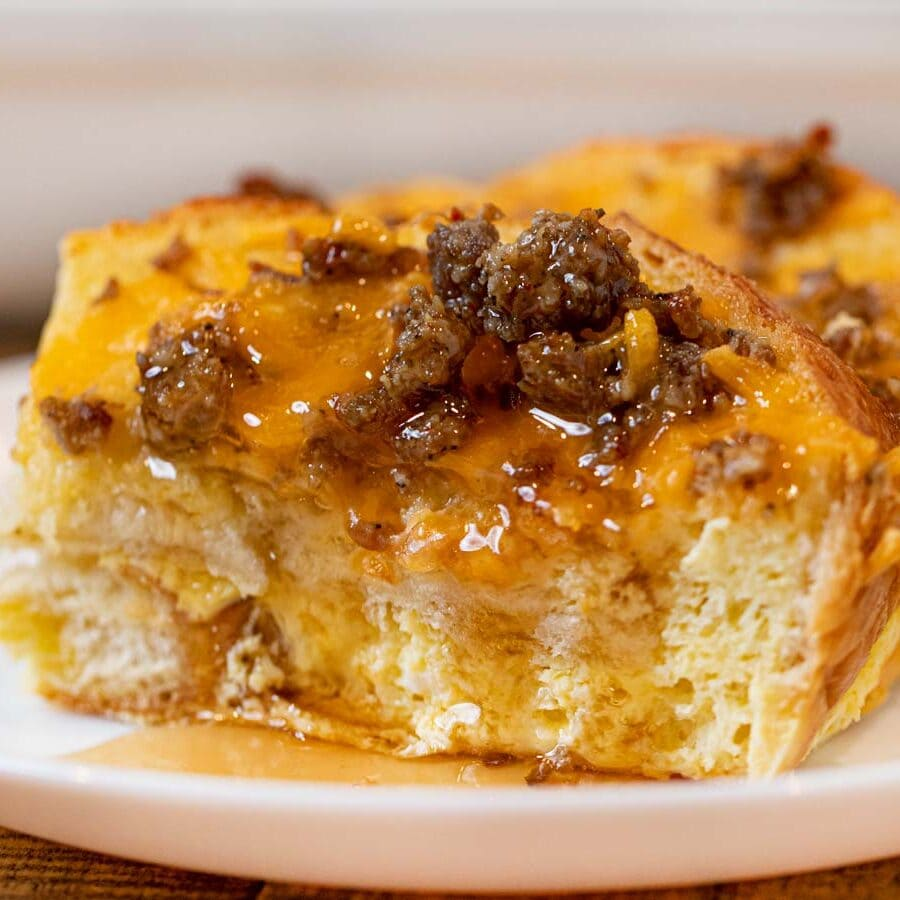 Sausage Cheddar French Toast Casserole slice on plate with maple syrup