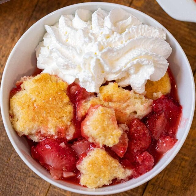 Strawberry Cobbler in bowl with whipped cream