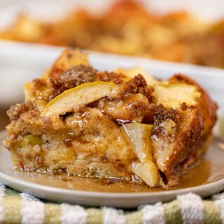 Sausage and Apple Breakfast Bake with syrup on plate and green napkin