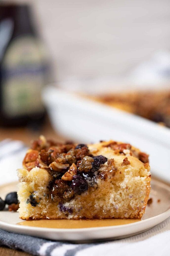 Slice of blueberry sausage pecan breakfast casserole on white plate with maple syrup
