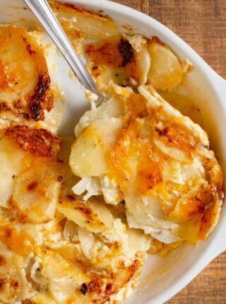 Cheesy Garlic Scalloped Potatoes serving on spoon