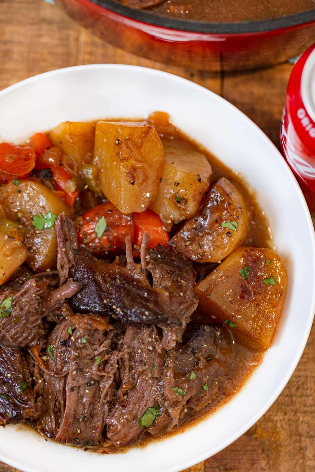 Coca Cola Pot Roast serving on plate with potatoes and carrots