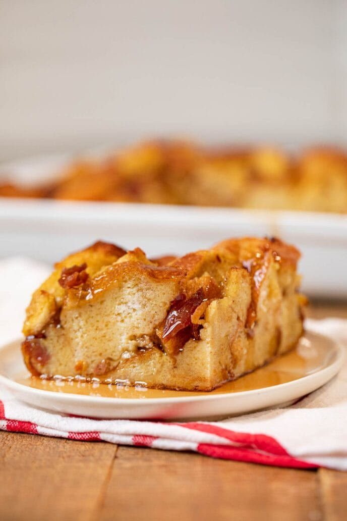 Square of Maple Bacon French Toast Bake on white plate with maple syrup