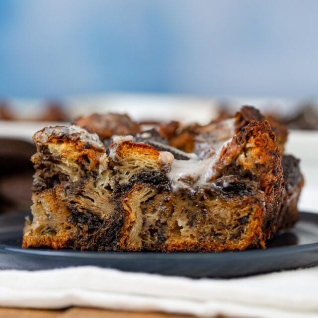 square slice of Oreo Croissant Bread Pudding on blue plate