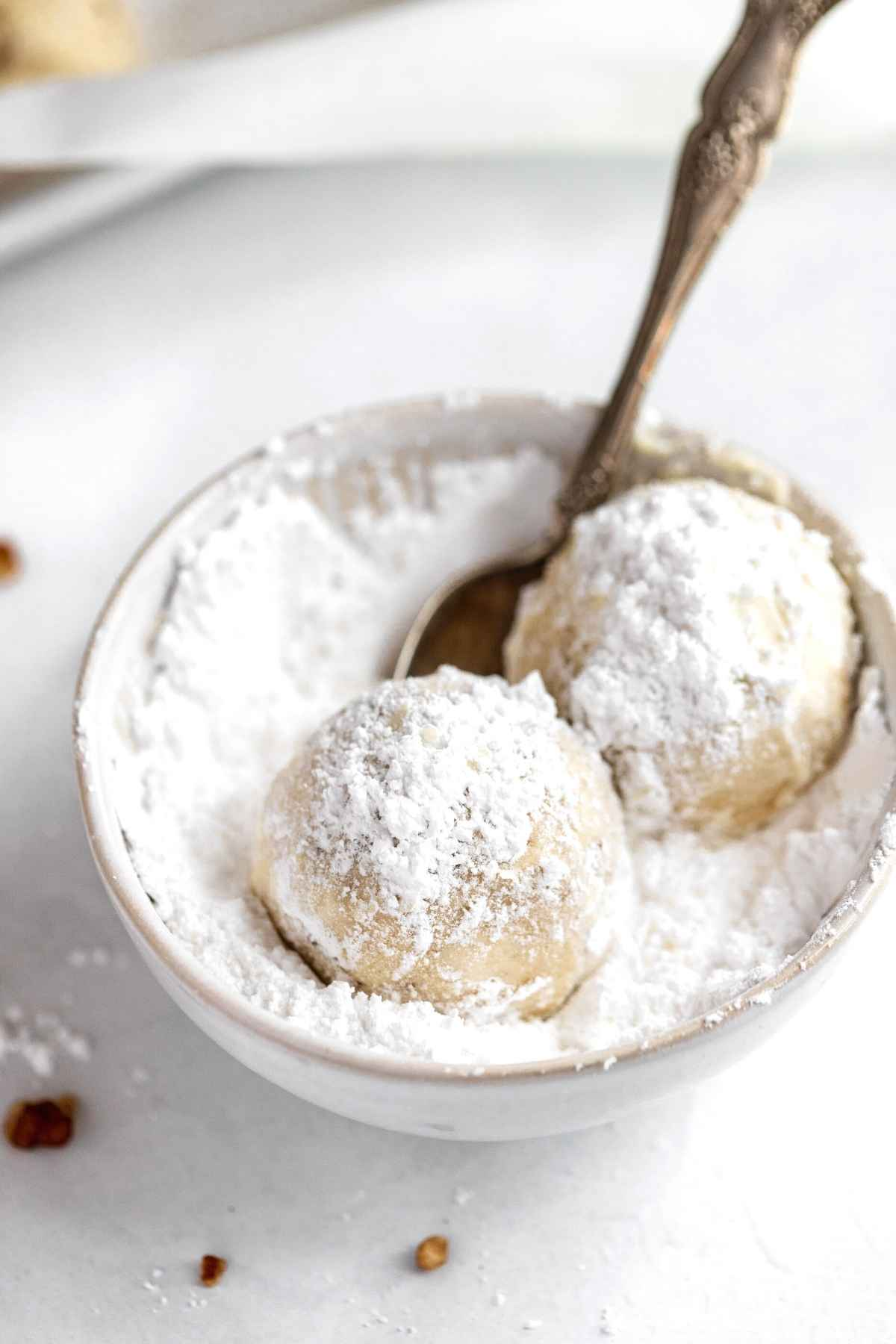 Snowball Cookies being rolled in powdered sugar in bowl with spoon