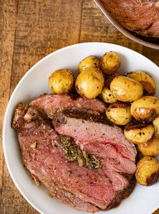 Stuffed Leg of Lamb on plate with potatoes