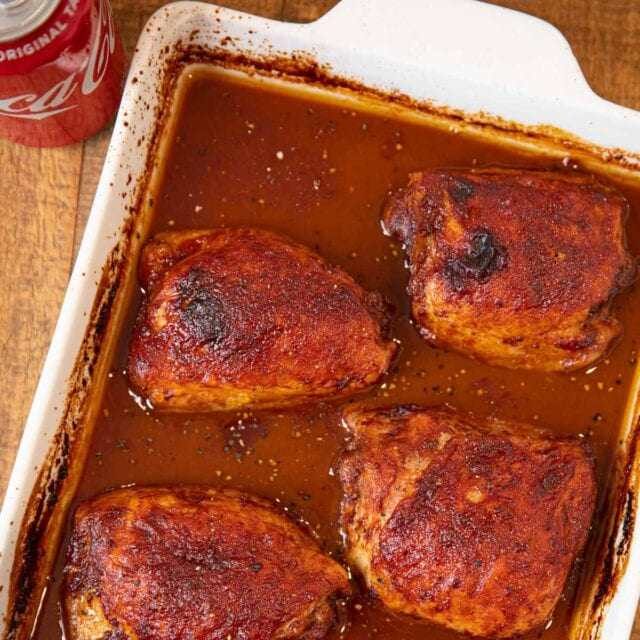 Coca Cola Chicken in white baking dish with can of Coca Cola on the side