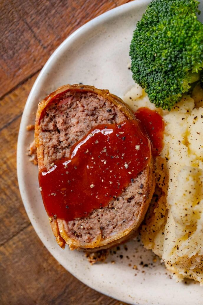 Bacon-Wrapped Meatloaf slice on plate with mashed potatoes and broccoli