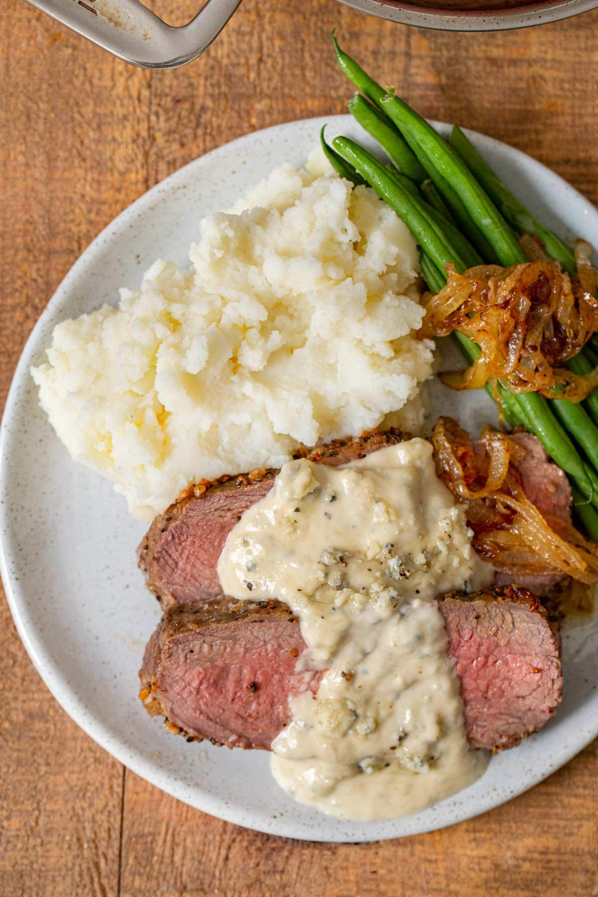 Blue Cheese Sauce over steak on plate