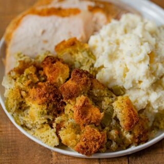Cornbread Dressing on plate with turkey and mashed potatoes
