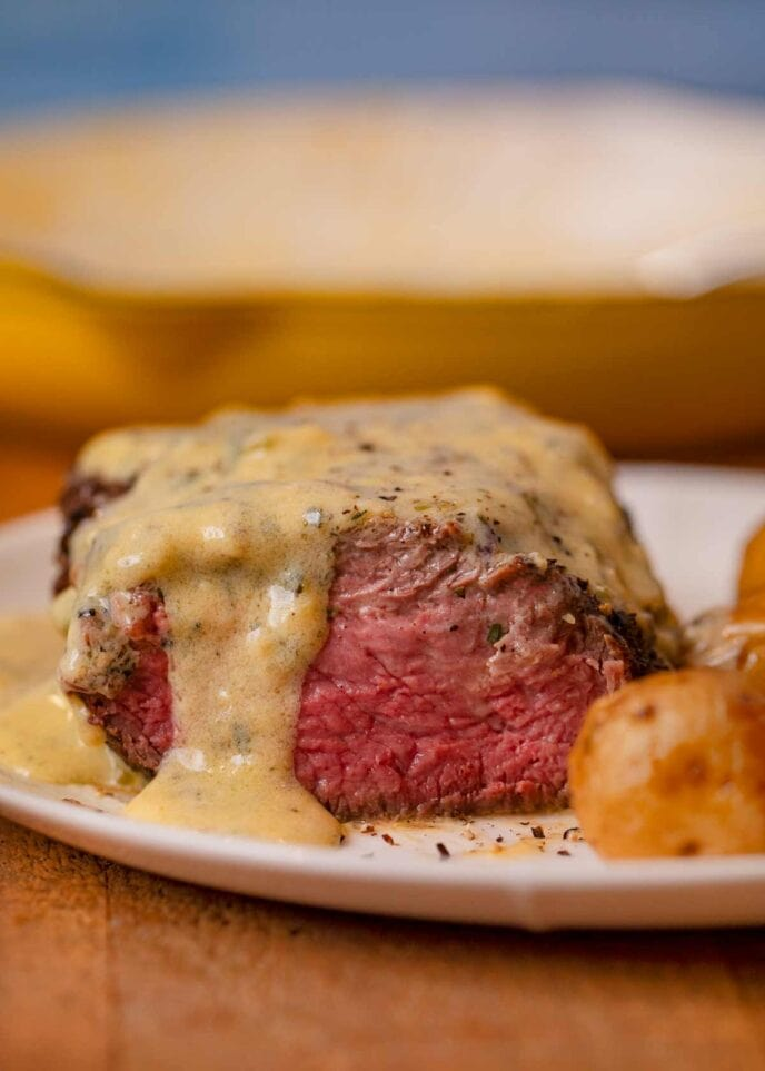 Filet with Bernaise Sauce, sliced open on plate with roasted potatoes