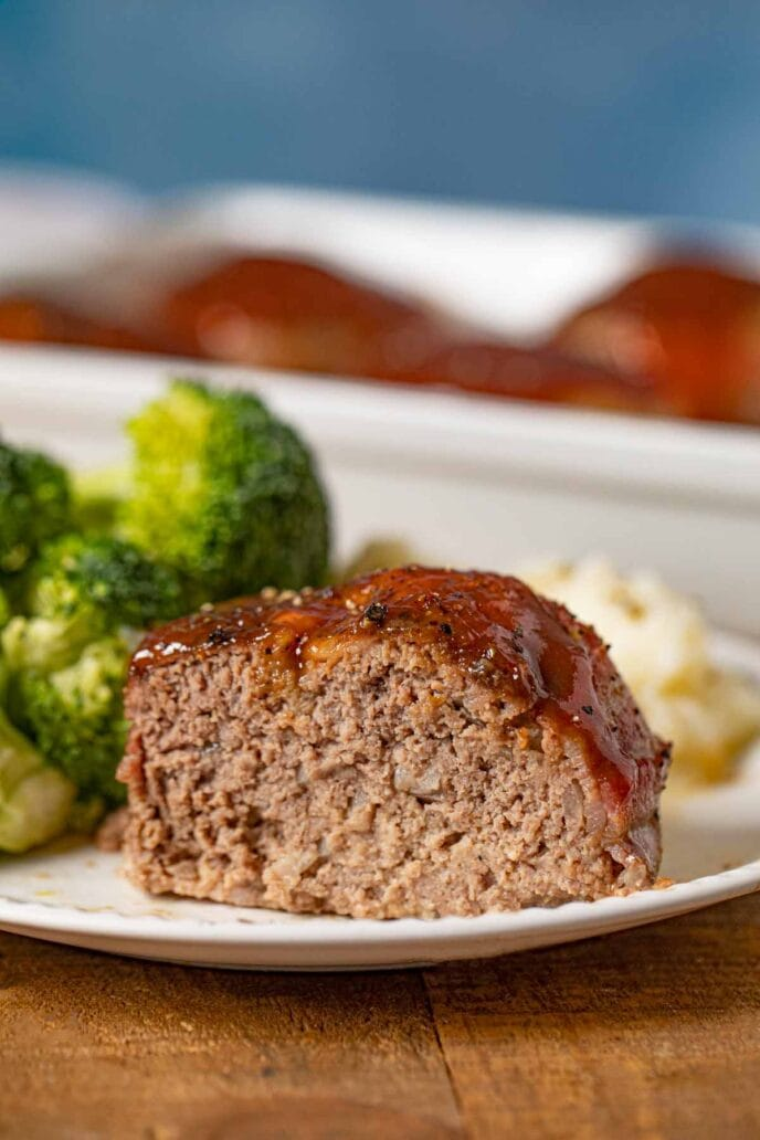Individual Bacon Wrapped Meatloaf on plate with mashed potatoes and broccoli