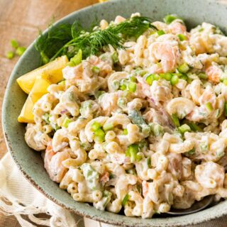 Creamy Shrimp Pasta Salad in serving bowl with fresh dill and lemon wedge garnish