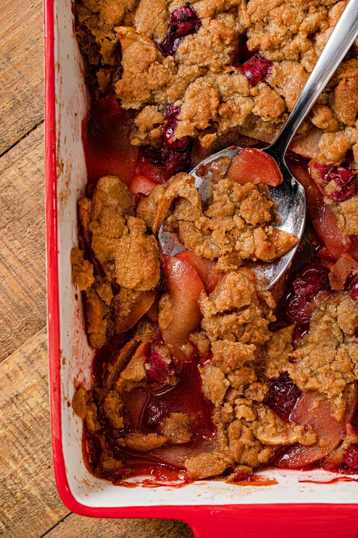 Apple Cranberry Crisp in baking dish with spoon