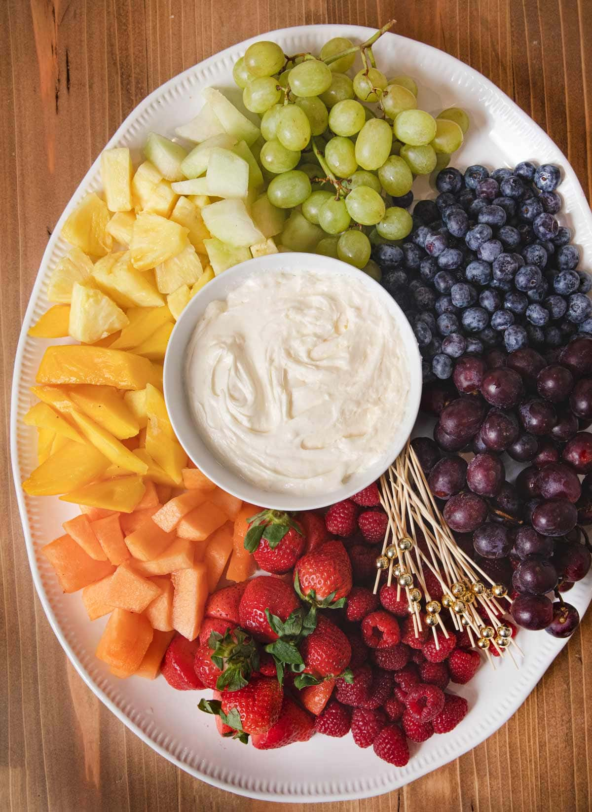 Fruit Dip in bowl in center of serving platter with rainbow fruit