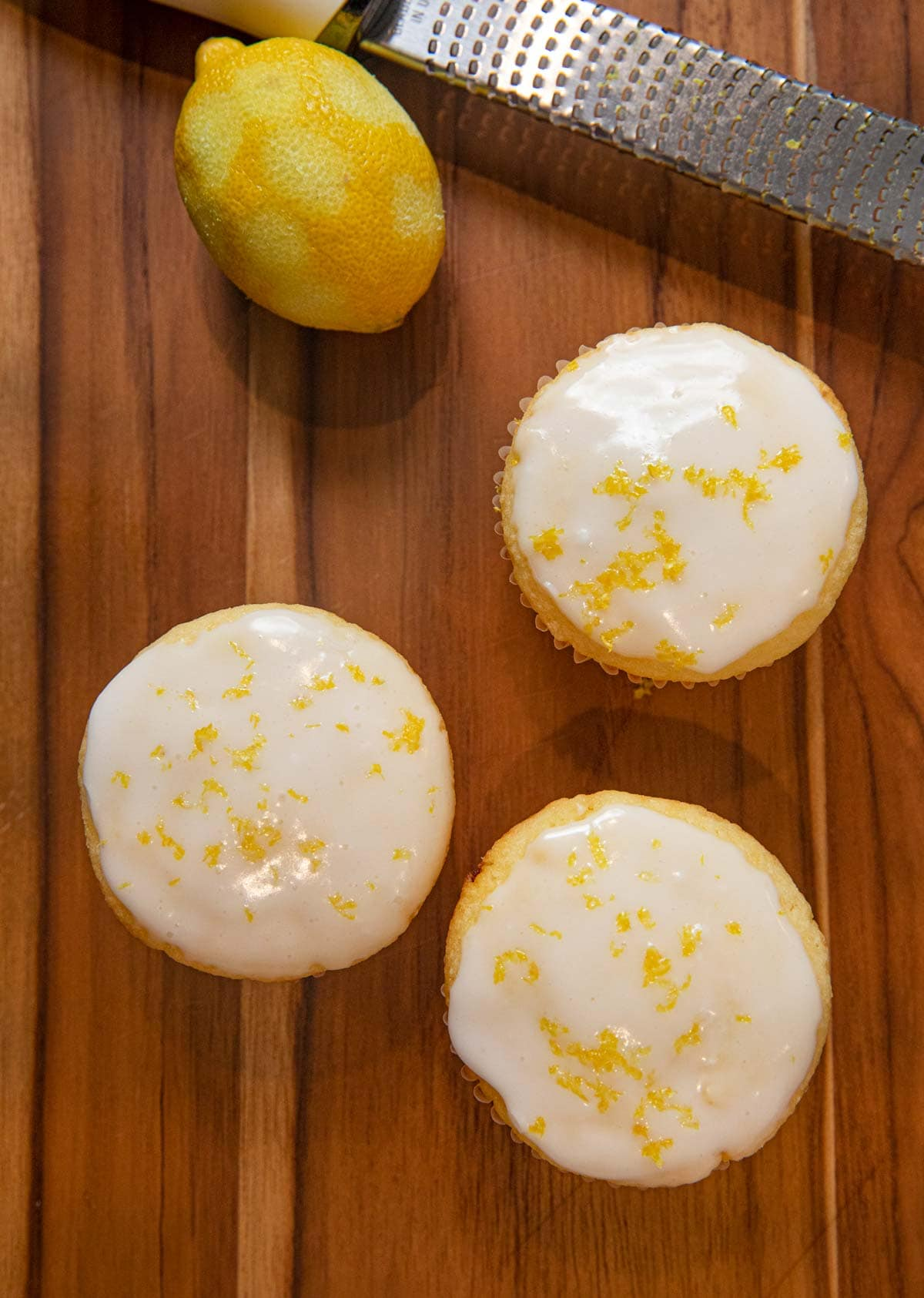 top-down view of Iced Lemon Muffins with zested lemon