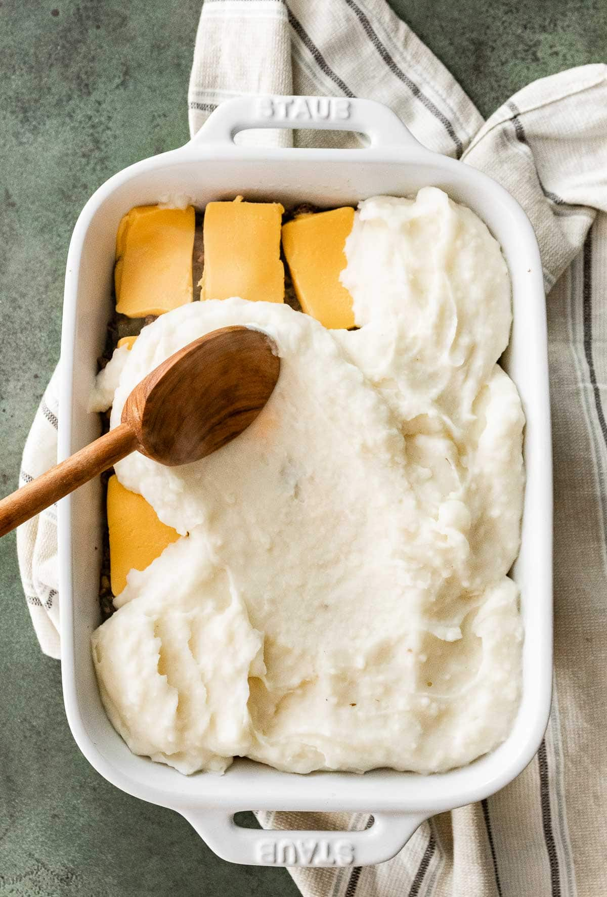 Assembling layers in baking dish for Philly Cheesesteak Shepherd's Pie