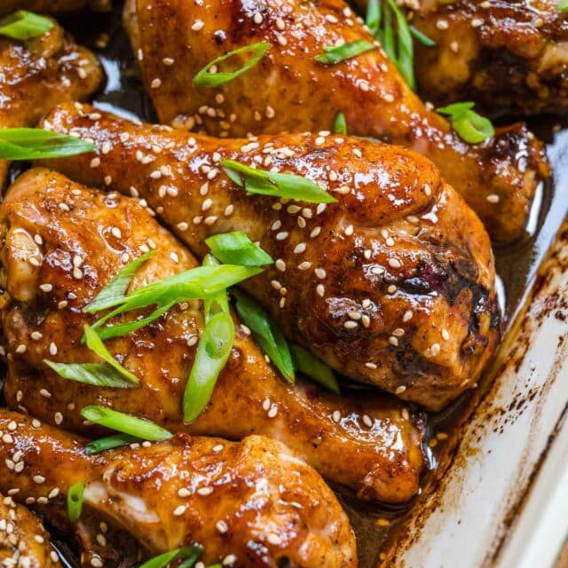 Brown Sugar Garlic Baked Chicken Legs sauce and chicken in baking dish with sliced green onions and sesame seeds