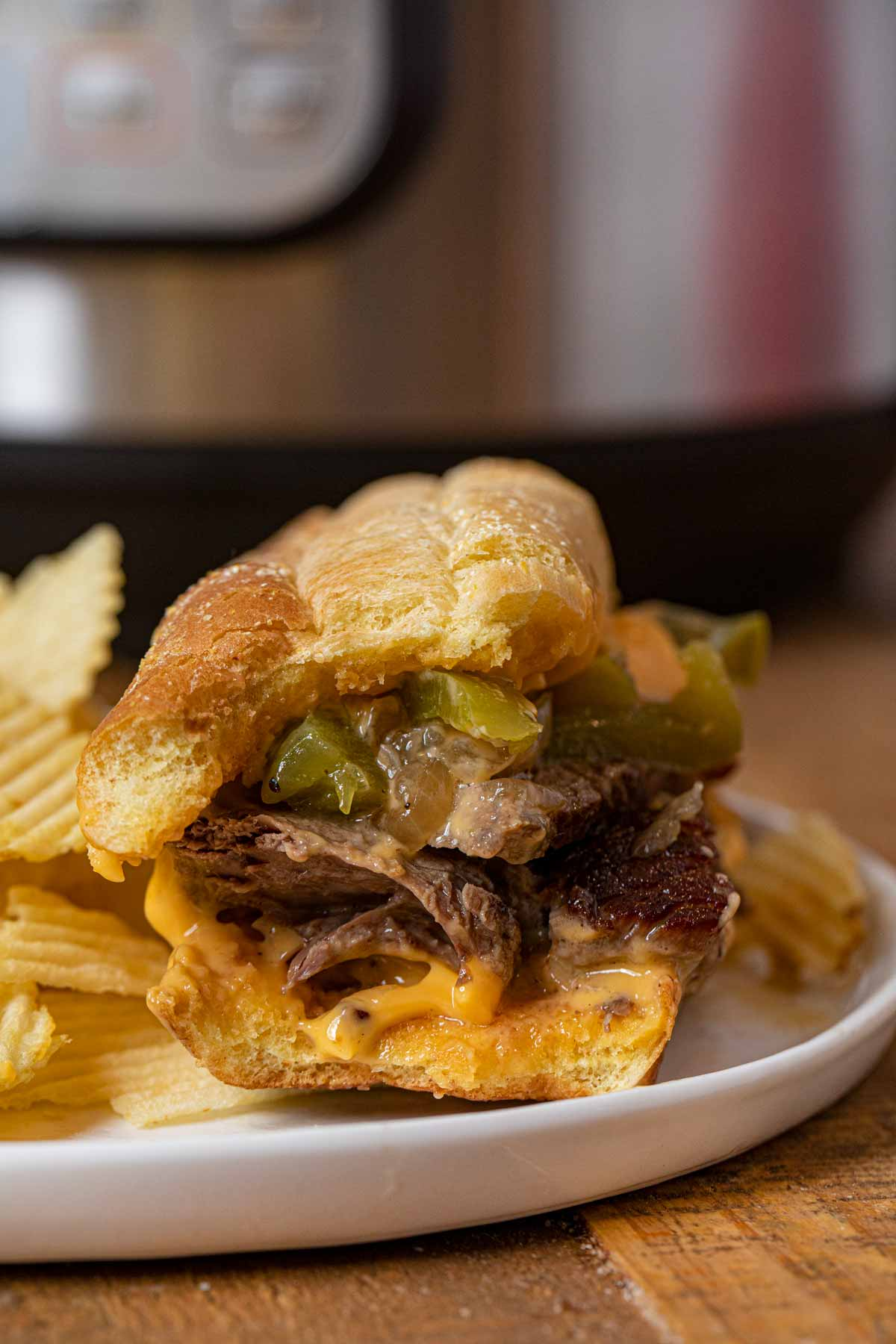 Instant Pot Philly Cheese Steak Sandwich partially eaten on plate with chips