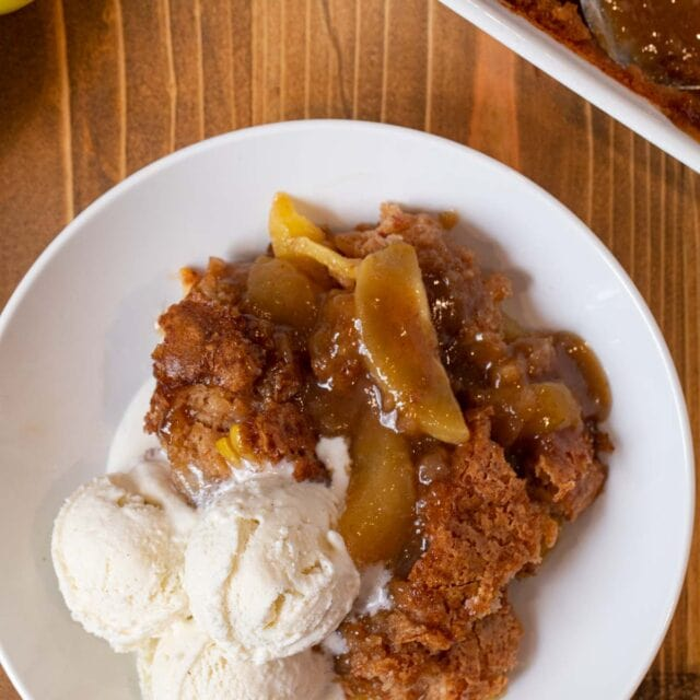 Caramel Apple Cobbler on a white plate with ice cream