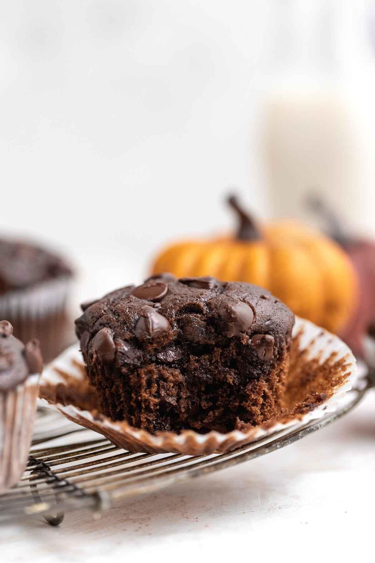 Chocolate Pumpkin Muffins on wire rack with bite taken