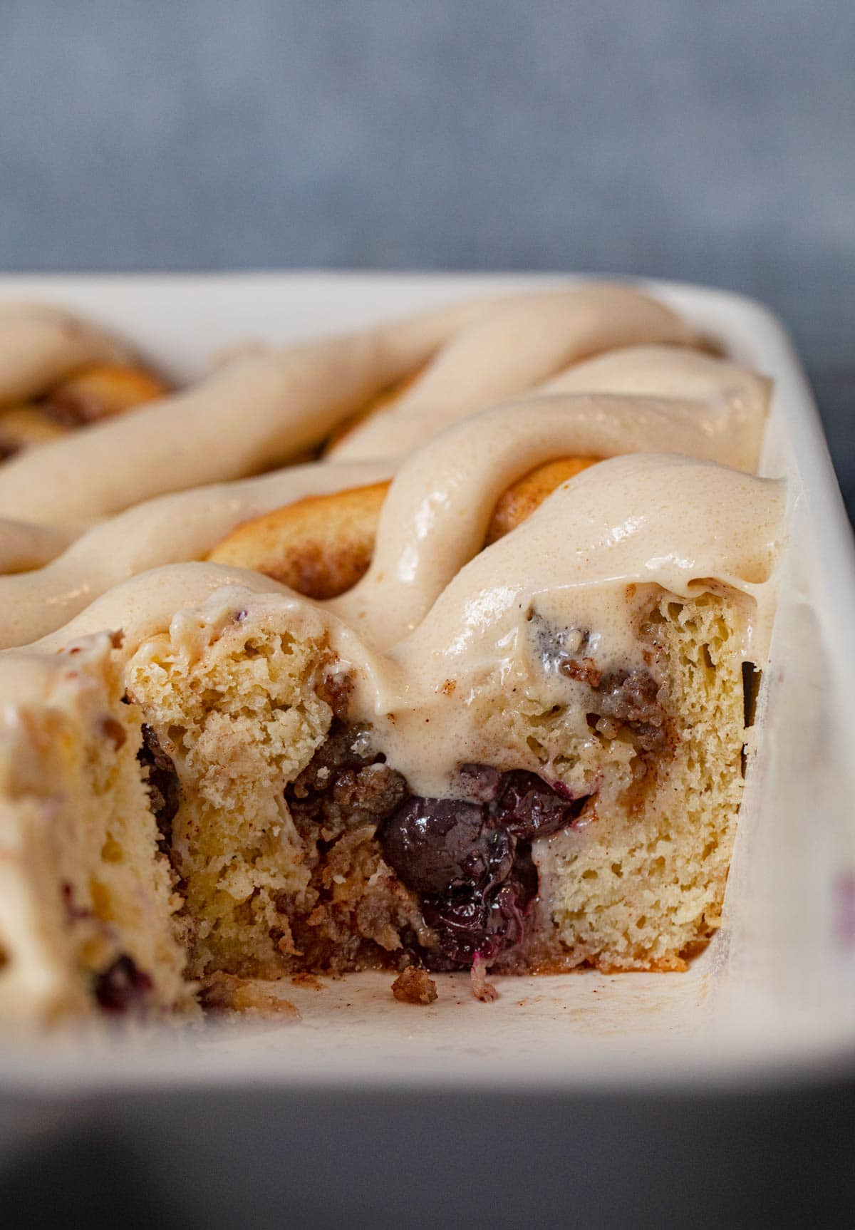 cross-section of Sausage Blueberry Cinnamon Rolls in baking dish