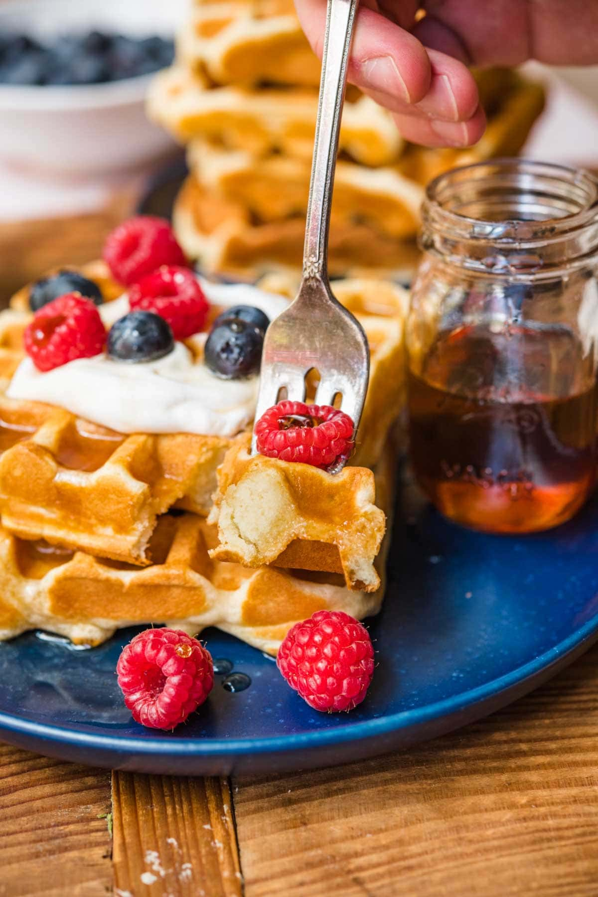 Classic Waffles on plate with whipped cream and berries