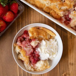 Strawberry Cream Cheese Cobbler serving in bowl with whipped cream