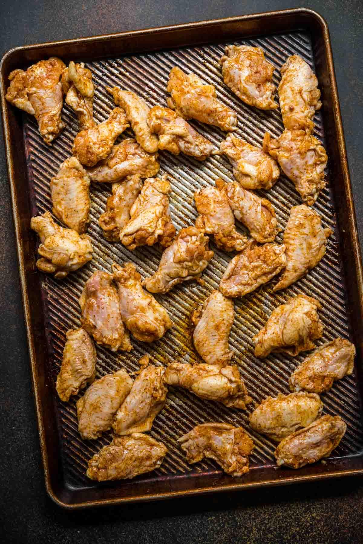 Baked Chicken Wings seasoned chicken wings on baking sheet before baking
