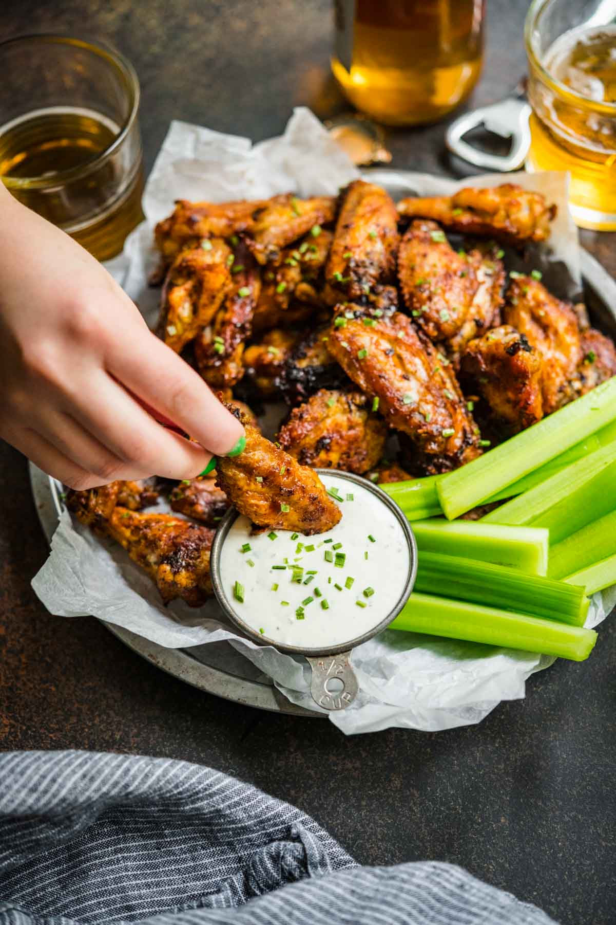 Baked Chicken Wings on serving plate with celery and hand dipping wing in creamy dip