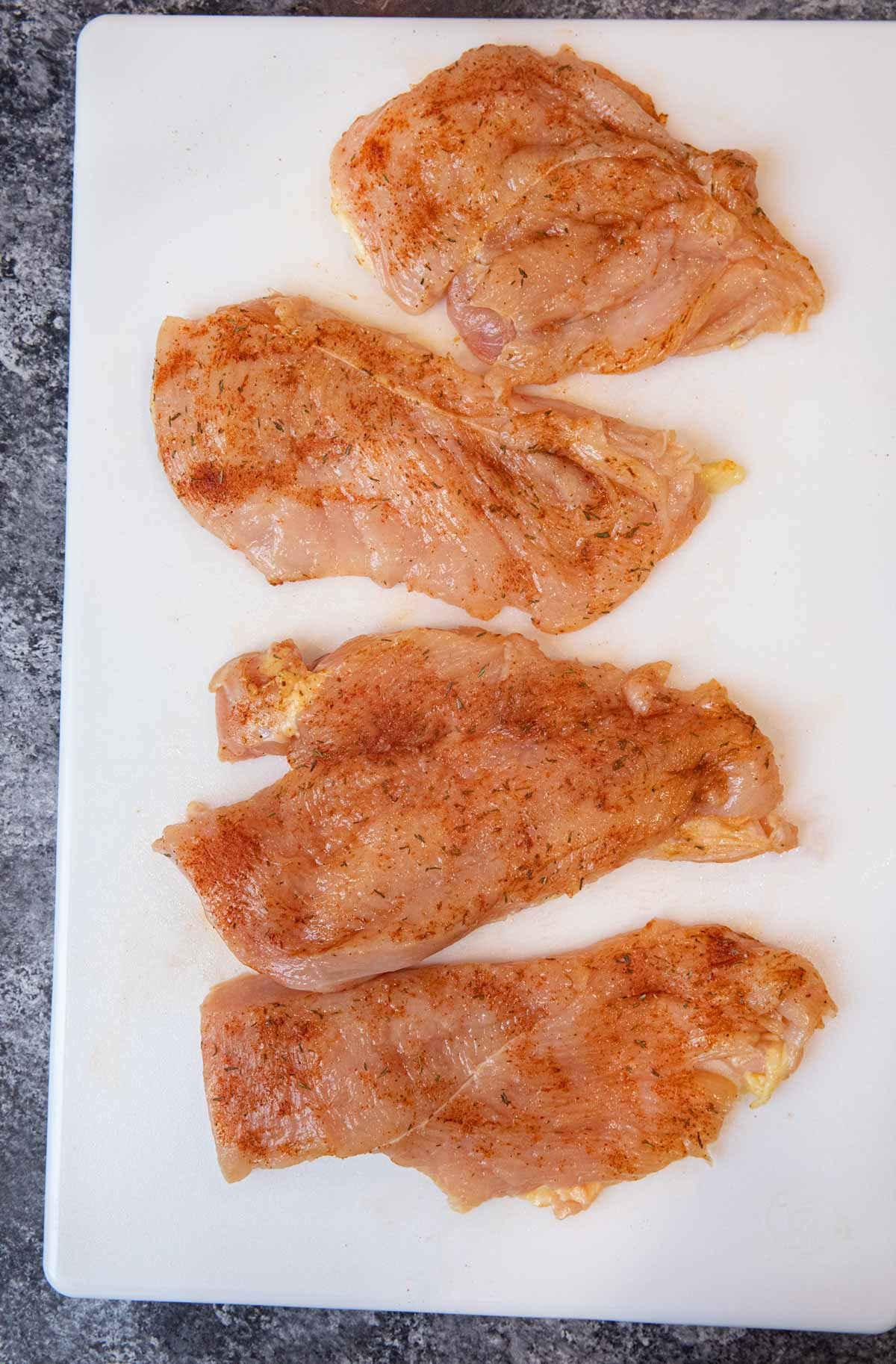 Blackened Chicken raw chicken breast coated with rub on cutting board